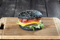 Large burger with a black buns Stock Photos