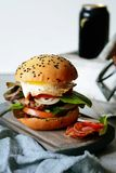 A large burger with a cutlet, vegetables, egg and a fresh roll. Sandwich for breakfast. Fast food. Men`s Food. Stock Photo