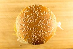 A large burger sprinkled with sesame top, cheese and salad. View from above royalty free stock photo