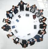 Large business team sitting at the round table and raising his hands up Royalty Free Stock Photos