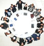 Large business team sitting at the round table and raising his hands up Royalty Free Stock Image
