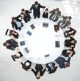 Large business team sitting at the round table and raising his hands up Stock Photography