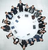 Large business team sitting at the round table and raising his hands up Stock Images