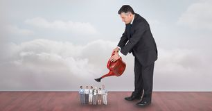 Large businessman watering employees against sky. Digital composite of Large businessman watering employees against sky Royalty Free Stock Photo