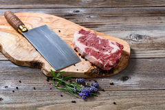 Large butcher knife and a fresh cut of seasoned beef ready to co Stock Photo