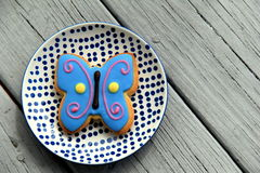 Large butterfly cookie frosted in bright colors, set on pretty plate Royalty Free Stock Images