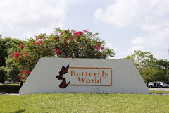 Large Butterfly World Sign Outside. Coconut Creek, FL, USA - July 21, 2015: Large cement and wood Butterfly World sign with butterfly graphics. White orange and Royalty Free Stock Photography