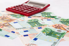 Large calculator on a lot of Euro banknotes cash Stock Photo