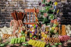 Child`s Dream of Candy Land. Large candy cane hanging on small red rocking chair surrounded by colorful assortment on candy Stock Photography