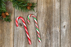 Large candy canes and evergreen branch on rustic wooded boards Stock Photography