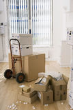 Large cardboard box on hand truck in office, small boxes on wooden floor near packing foam Royalty Free Stock Photos
