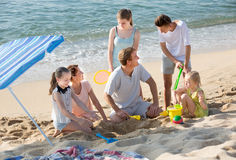 Large carefree family of six people on beach. Large carefree family of six people playing together with sand and active games on beach royalty free stock images