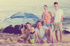 Large carefree family of six people together on beach. Sitting under umbrella and enjoying on weekend royalty free stock images