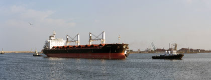 Large cargo carrier ship entering sea port  Stock Images