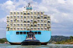 Large cargo ship being guided and towed through the Panama Canal carrying freights. Stock Photos
