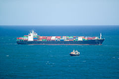 Large cargo ship bringing cargo containers to Durban, South Africa on the Indian Ocean Stock Images