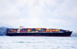 Large cargo ship carrying shipping containers. Large cargo ship in water carrying colorful shipping containers Royalty Free Stock Images