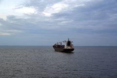 A large cargo ship floats by sea from the port of royalty free stock images