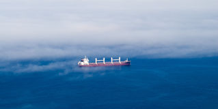 Large cargo ship in partial fog. Stock Images
