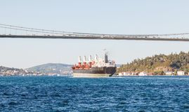 Large cargo ship proceeding along the Bosphorus Channel on the background of the bridge on the background.  Royalty Free Stock Image