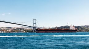 Large cargo ship proceeding along the Bosphorus Channel. On the background of the bridge on the background Royalty Free Stock Image