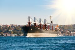 Large cargo ship proceeding along the Bosphorus Channel on the background of the coast on the background.  Royalty Free Stock Photo