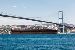 Large cargo ship proceeding along the Bosphorus Channel. On the background of the bridge on the background Stock Photos