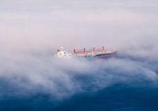 Large cargo ships in partial fog. Royalty Free Stock Photo