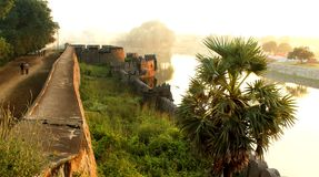 The large castle wall with palm tree sunset landscape at vellore. Big fort battlement with people landscape at Vellore. This  fort is a 16th-century fort Royalty Free Stock Photos