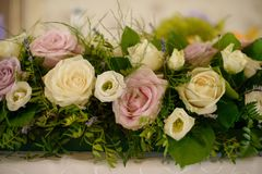 Large centerpiece with pastel color roses and fresh foliage. Horizontal close-up shot of table floral arrangement, suitable as a decor for table centerpieces at Royalty Free Stock Photos