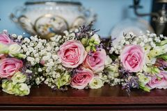Large centerpiece with pink and white roses and fresh foliage. Suitable as a decor for table centerpieces at a wedding reception ceremony or as an elegant stock photography