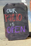 Large chalkboard sign that says ` Our patio is open, ` inviting people to come in and relax for awhile Royalty Free Stock Images
