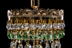 Large chandelier with green crystals close-up in baroque style isolated on black background. Royalty Free Stock Image