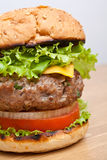 Large Cheeseburger close-up on wooden table. Large tasty cheeseburger close-up on wooden table Royalty Free Stock Images