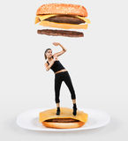 Large cheeseburger falling on a fit woman royalty free stock image