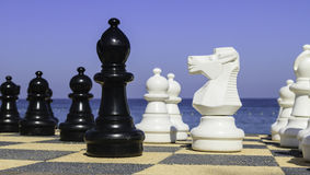 Large chess pices alongside the ocean Stock Images