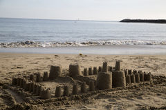 Large children's sand castle on the beach small ocean waves Stock Photos