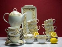 Large china tea-set with lemons on maroon Royalty Free Stock Images
