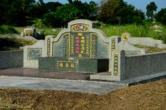 Large Chinese grave and tombstone with golden Mandarin writing at cemetery Ipoh Malaysia. Ipoh, Malaysia - June 3, 2017: A large, traditional Chinese grave of a stock images