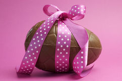 Large chocolate Easter egg with pink polka dot ribbon Royalty Free Stock Images