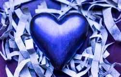 A large chocolate heart of purple color on strips of paper. Texture. Background stock photography