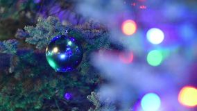 Large Christmas ball hanging on the Christmas tree in foreground blurry lights garland stock video footage