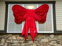 Large Christmas Bow. A large red bow is draped in front of a window to celebrate the Christmas season Royalty Free Stock Image
