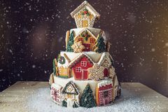 Large Christmas cake decorated with gingerbread cookies and a house on top. Concept of The desserts for the new year. Large tiered Christmas cake decorated with royalty free stock image