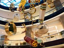 Large Christmas Decorations in Shopping Mall. Large and elaborate shiny Christmas, holiday season, decorations hanging in the void of an upmarket shopping mall stock photos