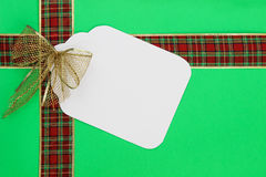 Large Christmas gift tag with red and gold ribbon on green wrapping paper background Stock Image