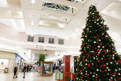 Large Christmas Tree in Mall. A large Christmas tree in a shopping mall in recognition of the holiday season. Holiday shoppers are walking around the mall Stock Photo