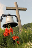 Large church bell hanging from a wooden cross. Large bell hanging from wooden cross in front of a newly restored historic church in Morrisville, New York Royalty Free Stock Image