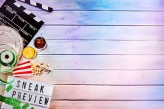 Large circular film reel next to food containers. Large circular metal film reel next to multiple food and drink containers and sign that says sneak preview in Stock Photo
