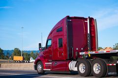 Big rig dark red semi truck tractor driving with flat bed traile Stock Images